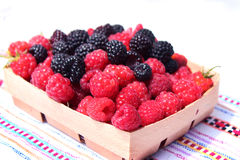 Black and red raspberries in wooden small box on the background Stock Photo