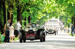 A black and red Riley prototype, followed by OOF classic cars. BRESCIA (BS), ITALY - MAY 14: A black and red Riley prototype, followed by OOF classic cars, takes Royalty Free Stock Image