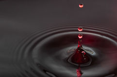 Black and red Water drops. A falling red water drops on a black surface water Royalty Free Stock Images