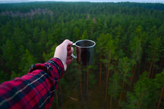 Black Red and White Plaid Pattern Long Sleeves Shirt While Holding a Stainless Steel Mug With a Forest Landscape Stock Photography