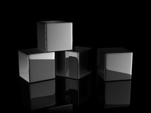 Black reflective cubes. Four black reflective cubes on dark background Royalty Free Stock Images