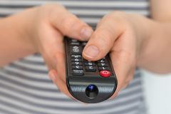 Remote control in female hands pointing to TV royalty free stock photos