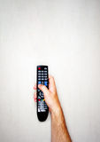Black remote control from the TV in a male hand on a light gray background. Top view Stock Photo