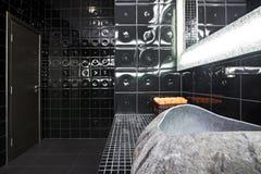 Black restroom. Interior of luxury black restroom with natural stone sink Stock Image