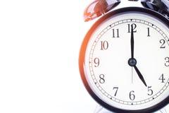 Black retro alarm clock with headphone isolated background on wh Stock Photos
