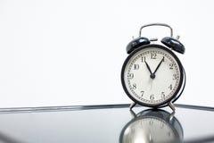 Black retro alarm clock on mirror table, toning.  stock image