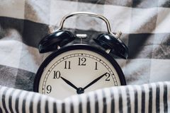Black retro alarm clock sleeping on pillow with blanket metaphor of insomnia, late at work, well sleep with time countdown or wake. Up in the morning stock image