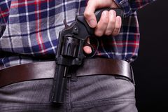 Black revolver behind the back royalty free stock photography