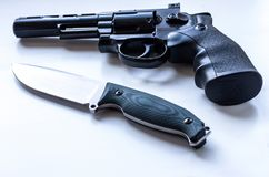 Black revolver with a drum and a knife with a fixed blade. royalty free stock images