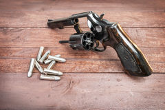 Black revolver gun with bullets isolated on wooden background Royalty Free Stock Images