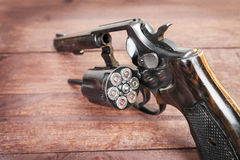 Black revolver gun with bullets  on wooden background Stock Images