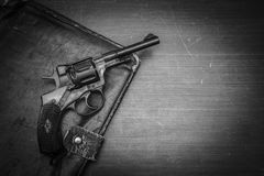 Black revolver on a wooden table. Black revolver with leather folder on the table stock images