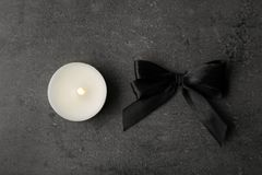 Black ribbon and candle on grey background. Top view. Funeral symbols stock photos