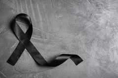 Free Black Ribbon With Space  Text On Grey Stone Background, Top View. Funeral Symbol Stock Photos - 158201263