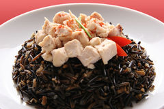 Black rice. Black rice with boiled chicken breast on a white plate Royalty Free Stock Photography