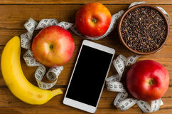 Black rice, banana, apple, smartphone and measuring tape on a wo Royalty Free Stock Photography