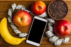 Black rice, banana, apple, smartphone and measuring tape on a wo Royalty Free Stock Photo