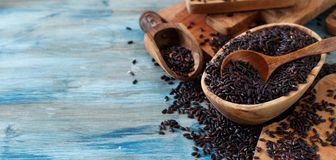 Black rice in a bowl with a spoon. On a wooden table close up Royalty Free Stock Photography