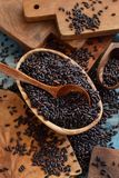 Black rice in a bowl with a spoon. On a wooden table close up Royalty Free Stock Image