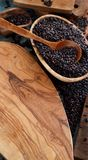 Black rice in a bowl with a spoon. On a wooden table close up Royalty Free Stock Photos