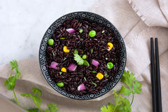 Black rice in a bowl and vegetables on marble table Stock Images