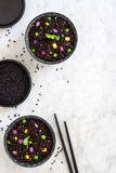 Black rice in a bowl and vegetables on marble table Stock Image