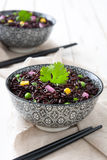 Black rice in a bowl and vegetables on white wooden table Stock Image