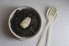 Black rice with cuttlefish, on w. Black rice with cuttlefish, on black cement dish and grunge background Stock Images