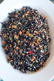 Black rice dish seasoned with tomatoes , carrots , olive oil and stock images