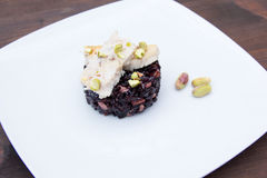 Black rice with fish and pistachios on wooden seen up close Stock Photos