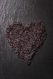 Black rice in heart shape on a black stone background with water droplets Royalty Free Stock Images
