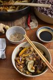 Black rice noodles with stir fried vegetables in a bowl, with so. Portrait view of stir fried vegetables with black rice noodles in a bowl, sesame seeds, soy Stock Photos
