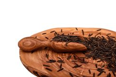 Black rice on an olive board with a wooden scoop isolated on a white background Stock Image