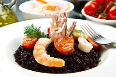Black rice with sliced squids ,prawns and tomato Stock Images