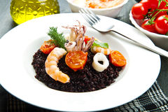 Black rice with sliced squids ,prawns and tomato Stock Image