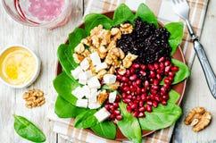 Black rice spinach feta pomegranate walnut salad with orange hon Stock Image