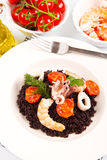 Black rice with squid , prawns and tomatoes Royalty Free Stock Image