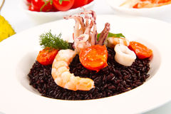 Black rice with squid , prawns and tomatoes Stock Photography