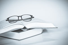 Black rimmed glasses placed on opened book Royalty Free Stock Photography