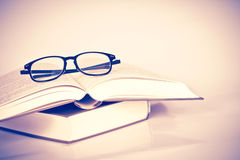 Black rimmed glasses placed on opened book Royalty Free Stock Photo