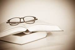 Black rimmed glasses placed on opened book Stock Photography
