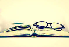 Black rimmed glasses placed on opened book Stock Images