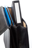 Black ring binder in an open briefcase. Black file folder looking out of an open brieface (with a second folder inside). White label for copy Stock Photo