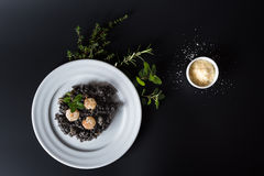 Black risotto with herbs and parmesan Stock Image