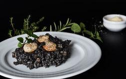 Black risotto with herbs and parmesan Royalty Free Stock Photo