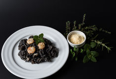 Black risotto with herbs and parmesan Stock Photo