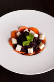 Black risotto with sliced carrots and cheese on white plate. Vertical Stock Image