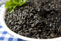 Black risotto. On a white plate garnished with persil Royalty Free Stock Photography