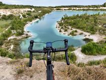 Black road bicycle on the edge of cliff blue lake in front stock photo