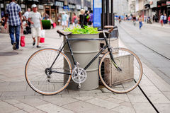 Black Road Bike Leaned on Gray Steel Drum Beside Street With People at Daytime Royalty Free Stock Photography